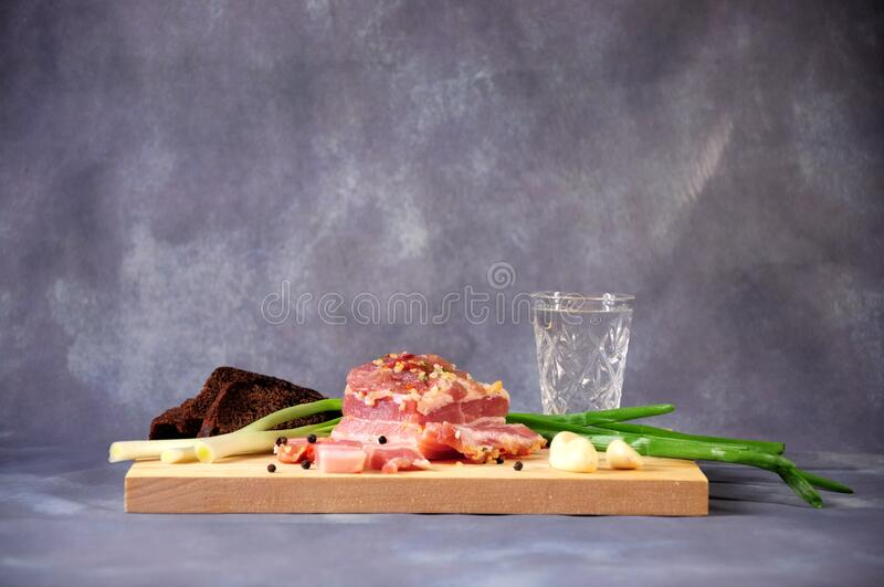 A wooden stand with a glass of cold Russian vodka next to green onions, garlic, a piece of bacon and slices of rye bread royalty free stock images