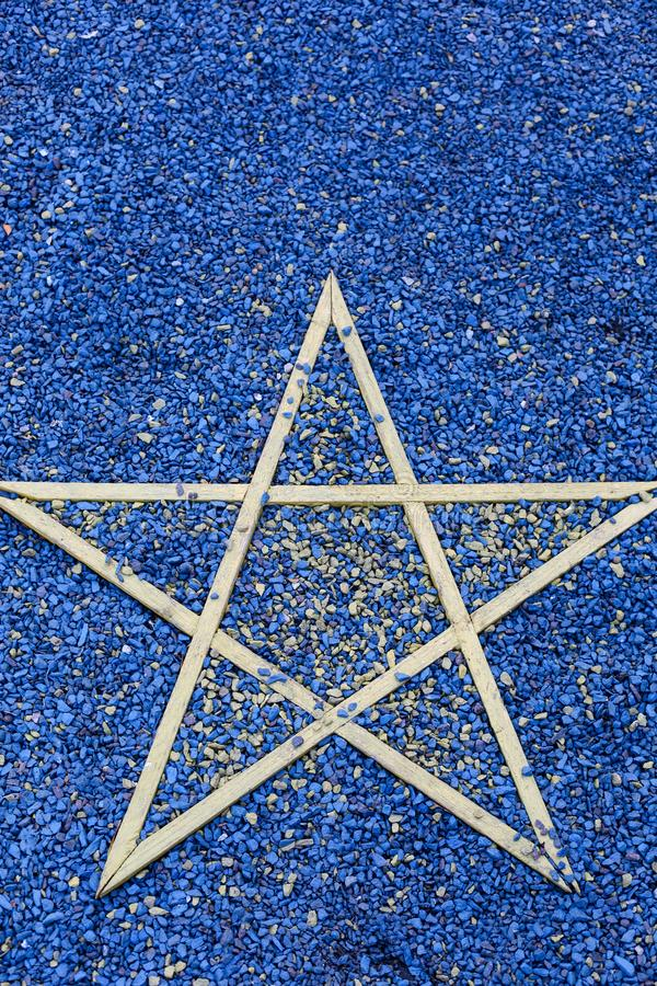 Wooden star on blue stones. Symbol of the European Union. Vertically framed shot royalty free stock photos