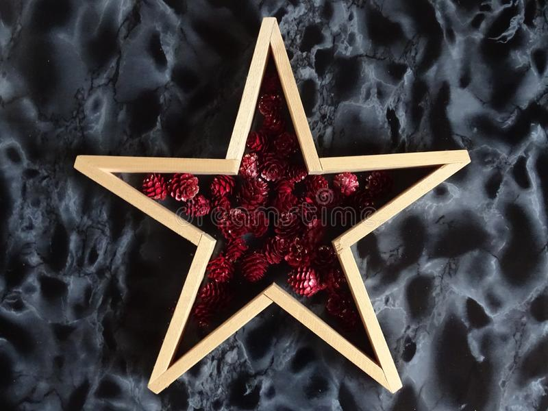 Wooden star on dark marble background. Wooden star filled with red pineapples on dark marble blackground royalty free stock photos