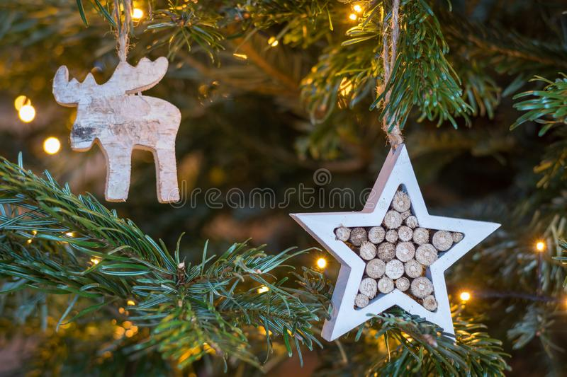 Wooden star and moose ornament hanging on a Christmas tree with stock images