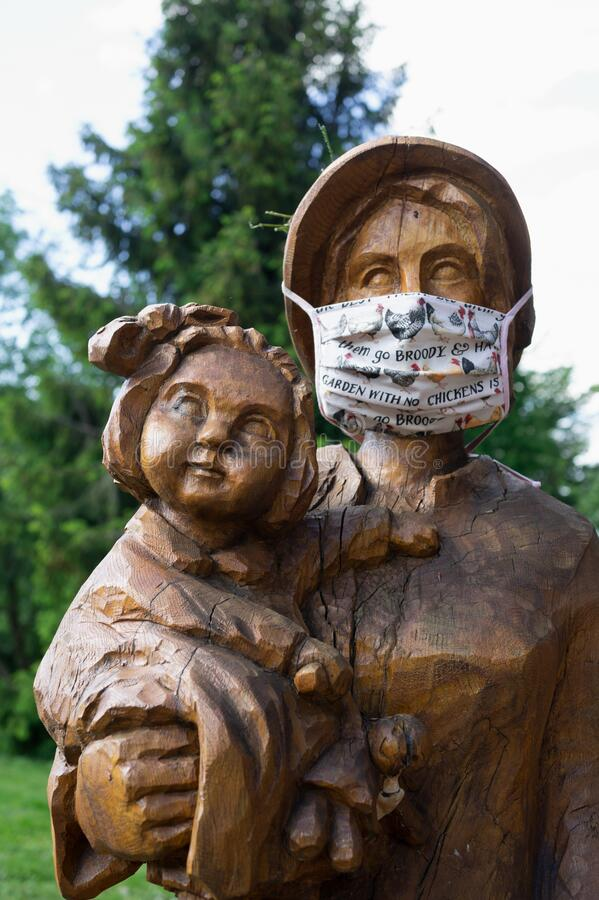 Wooden statues of mother and child are wearing face mask royalty free stock image