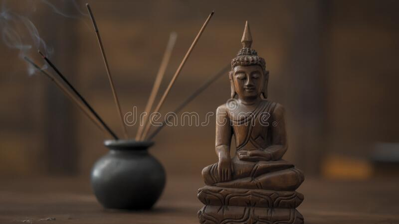 Wooden statuette of Buddha incense sticks at workplace. Abstract picture of a modern office in oriental style, selective. Focus on smoking incense sticks and royalty free stock images