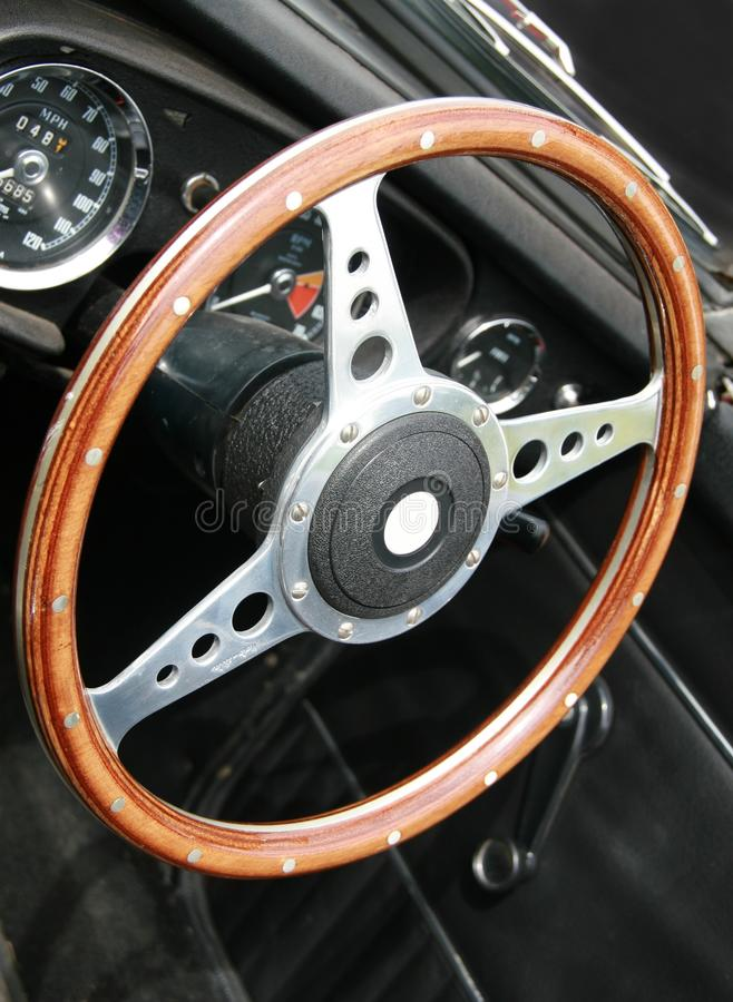 Wooden steering wheel - MGB roadster. Wooden steering wheel from a classic MGB roadster car royalty free stock images