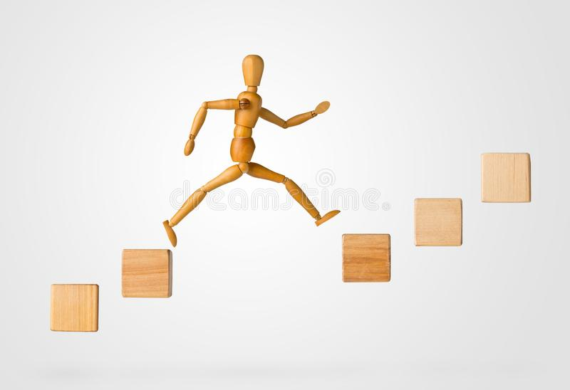 Wooden stick figure jumping from one wooden block on rising steps to the next - achievement, career or objective concept on white royalty free stock photos