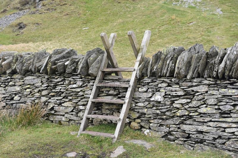 Wooden stile over stone wall stock photo