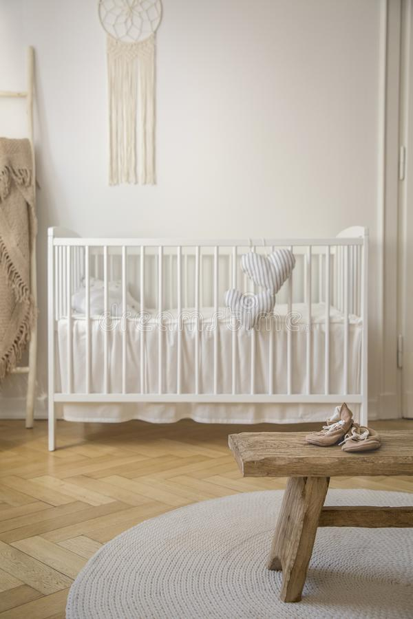 Wooden stool with shoes on round rug in bright baby`s bedroom interior with white cradle. Real photo stock photography