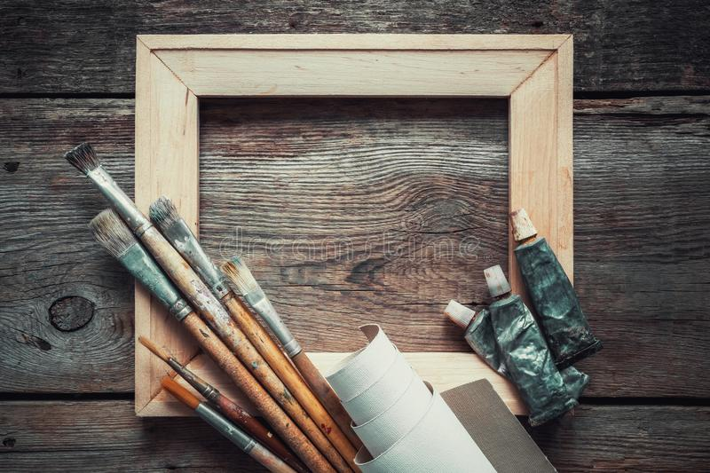 Wooden stretcher bar, paintbrushes, roll of artist canvas and paint tubes. stock photos