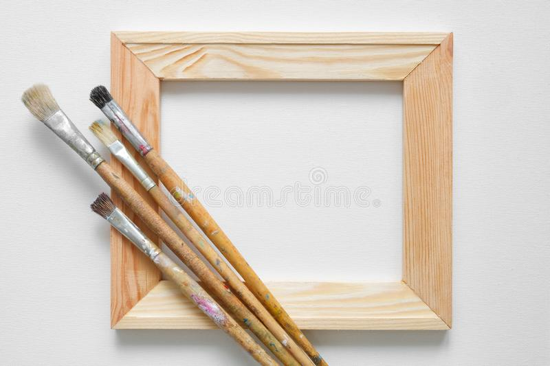 Wooden stretcher bar and paintbrushes on white artist canvas background. stock image