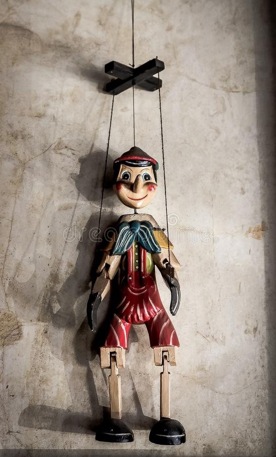 Wooden String Puppet Boy hanging on a wall. Selective Focus Abstract image of a Wooden String Puppet Boy hanging on a wall royalty free stock photo