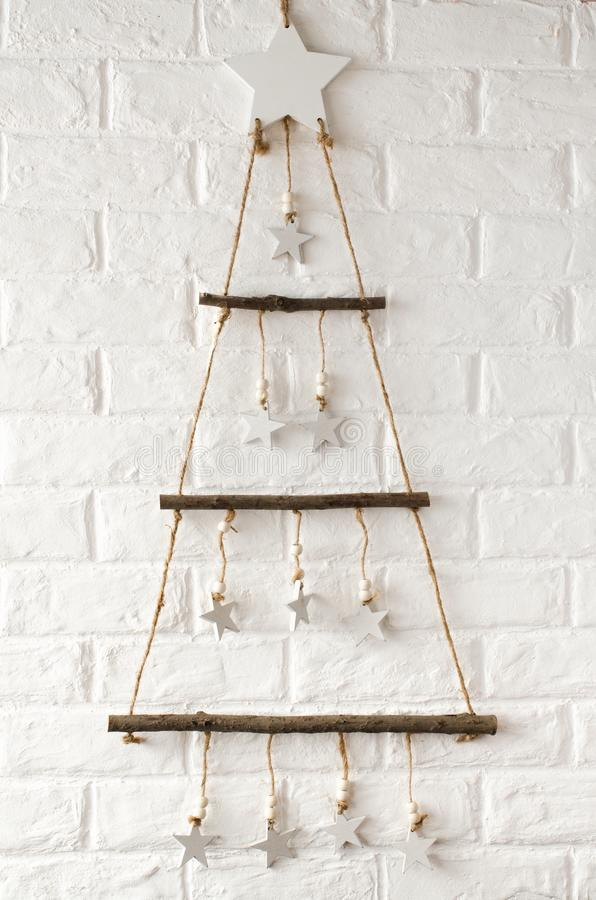 Wooden stylish Christmas tree in scandinavian style against the background a white brick wall. Simple minimalistic Christmas and New Year home decor royalty free stock photography