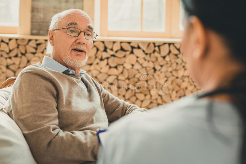 Intelligent sage pensioner questionable looking on his nurse. Wooden stylish room. Intelligent sage pensioner questionable looking on his nurse while everyday royalty free stock photos