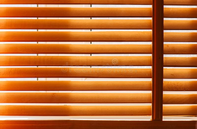 Wooden sun blinds on window. With sun light stock photos