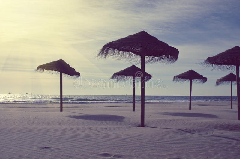 Wooden sun umbrellas silhouettes on the sea beach. Vacation concept in vintage color tone. Costa Dorada, Spain royalty free stock images