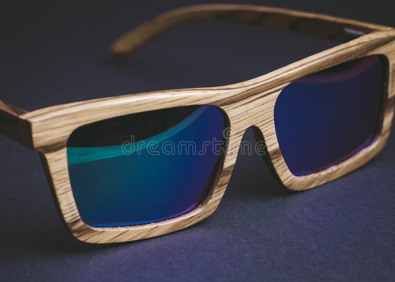 Wooden sunglasses detail. On a dark background stock image