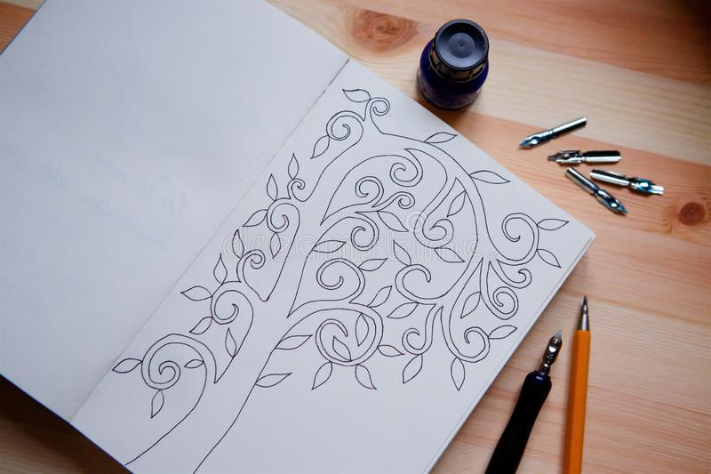 On the wooden surface is an open notebook with a sketch in the form of a tree with leaves royalty free stock image