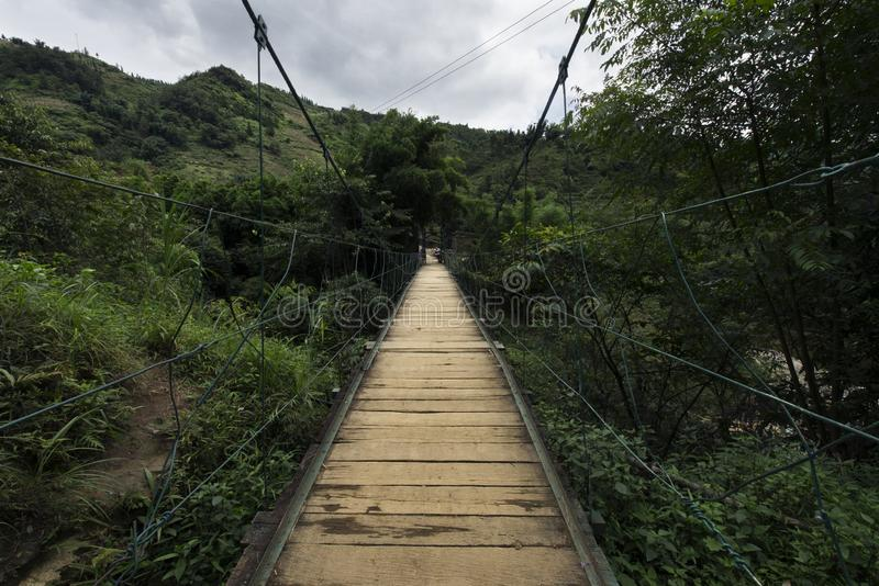Wooden suspension bridge in the forest of Sapa, Lao Cai, Vietnam royalty free stock image