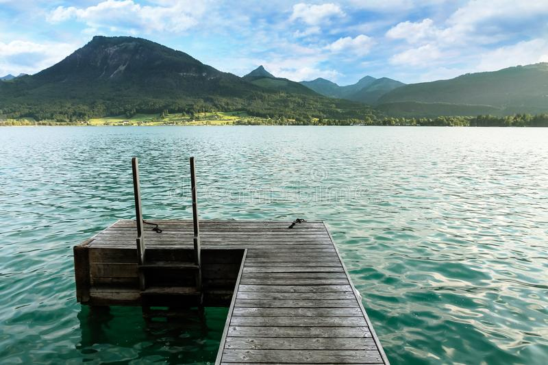 Wooden swimming platform as bridge pier deck on alpine lake with beautiful green turquoise clear water during Summer royalty free stock photo