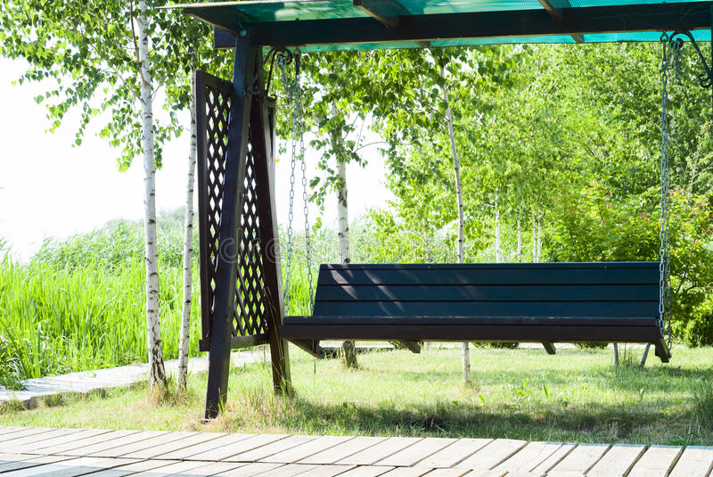 Wooden swing. On the background of the birches royalty free stock image