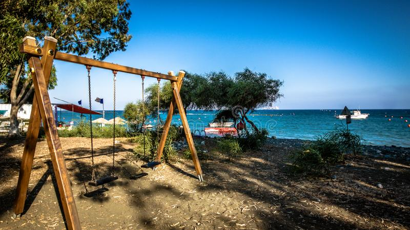 Wooden swing on the Beautiful beach. Sunbeds with umbrella on the sandy beach near the sea. Summer holiday and vacation concept. I stock photos