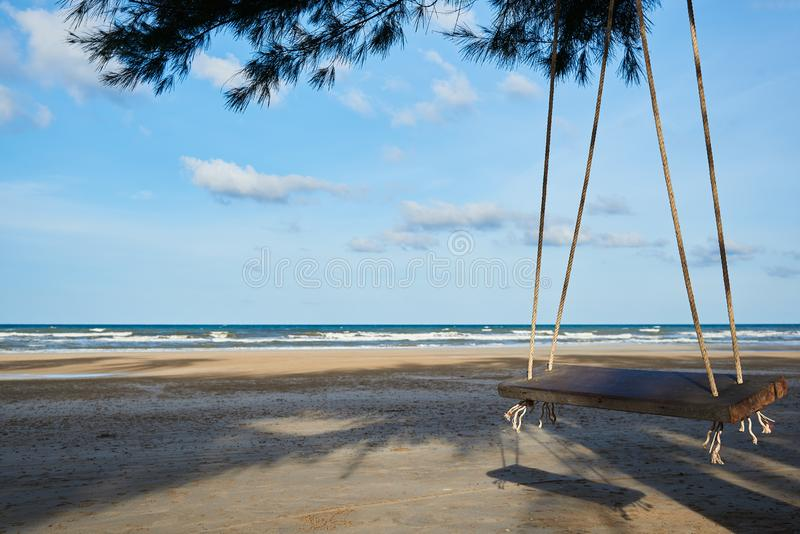 A wooden swing on the beautiful blue sky and sea background. A wooden swing hanging on the tree on the beautiful blue sky and clouds background. Morning sunlight royalty free stock photo