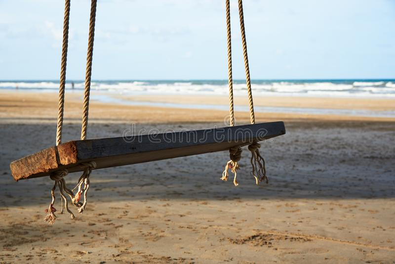 A wooden swing on the beautiful blue sky and sea background stock photos