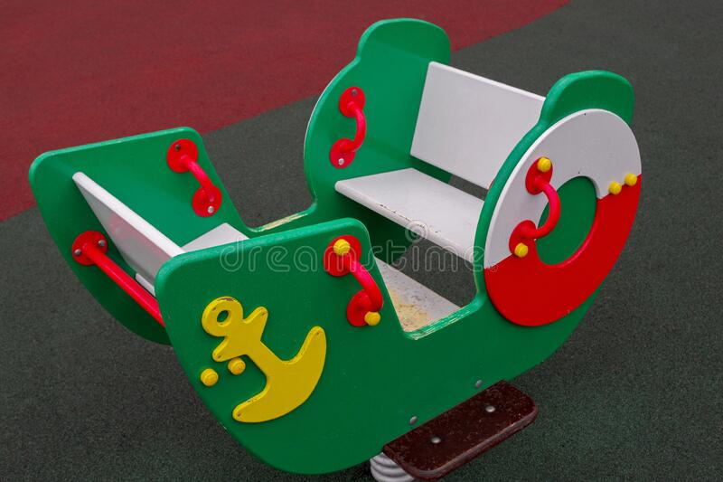 Wooden swing-boat mounted on powerful spring, painted green with white seats inside with yellow anchor and red and white lifebuoy. Wooden swing-boat mounted on a royalty free stock photography