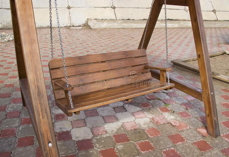 Wooden swing on chains stock photo