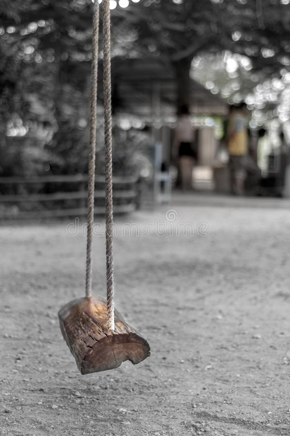 Wooden swing hang by rope at playground. Empty wooden swing hang by rope at playground, on pale and blurred background royalty free stock photo