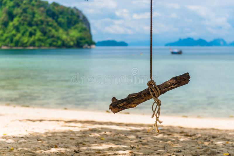A wooden swing on a rope in the shade of a tree. In a heavenly tropical place on the island royalty free stock photo