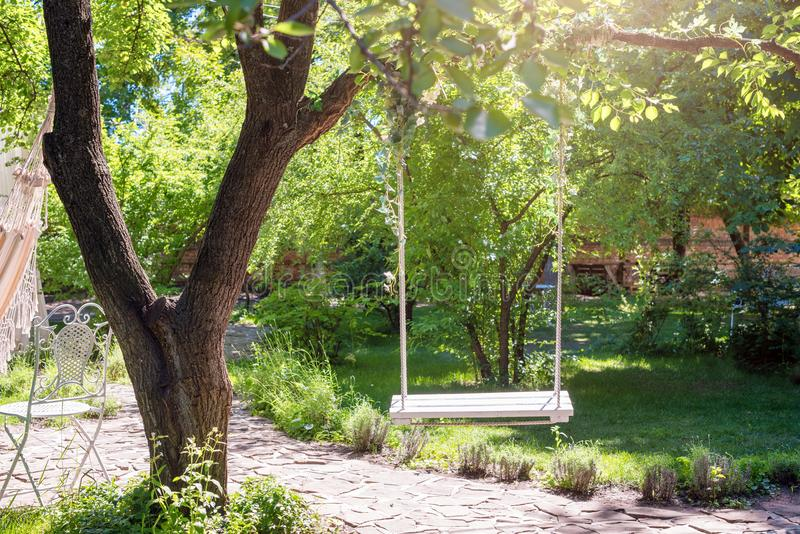 Wooden swing on ropes under the big tree in the garden. stock photography