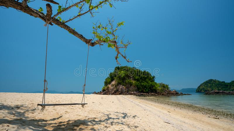 Wooden Swing On The Beach. Wooden Swing On Tree Branch With Sunlight Sea Sand Beach stock images