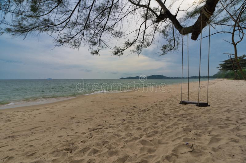 Wooden swing under the tree close to the sand beach and white clear water.at Beach sea Ra yong Thailand.  royalty free stock image