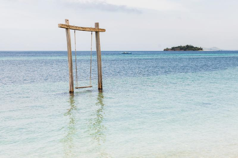 Wooden swing in water on beach. Holiday and vacations concept, tropical island stock images