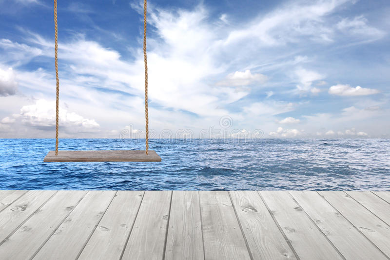 wooden swing and wood floor on sea wave in blue sky background. royalty free stock photos