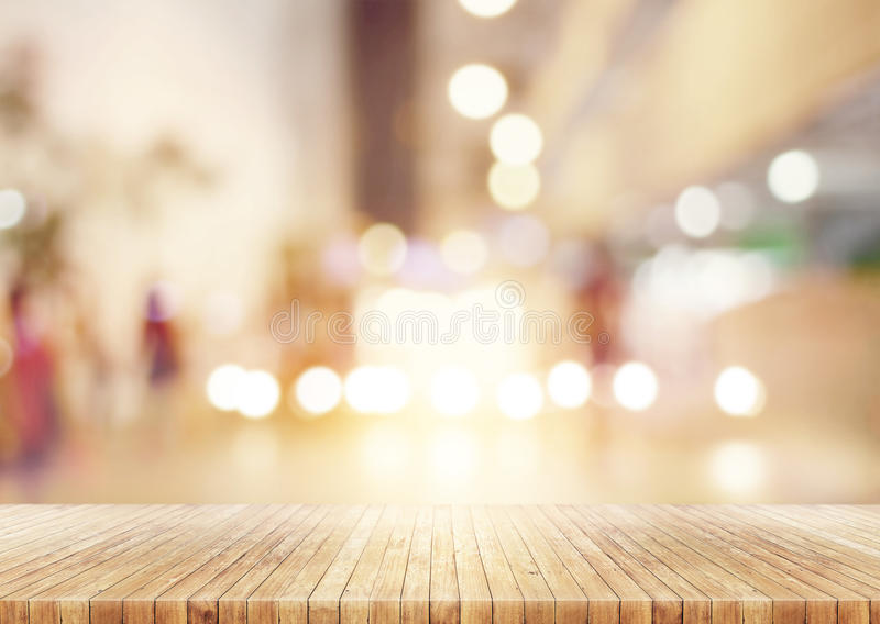 Wooden table in abstract blurred background of shopping mall royalty free stock photos