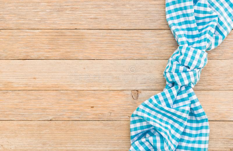Checked blue napkin on wood table background, top view, copy space. Wooden table background with blue checkered tablecloth, high angel view royalty free stock photography