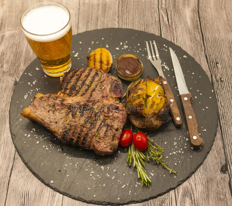 On wooden table background juicy beef steak with a glass of light beer foam. royalty free stock photos