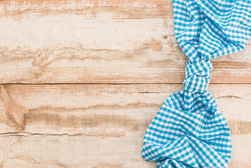 Light blue checked tablecloth knotted above rustic wooden table background with copy space. Wooden table background rustic texture, with blue checkered royalty free stock image