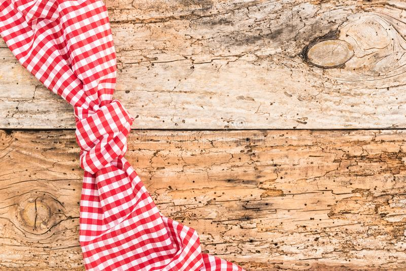 Old wooden picnic table background with rustic red checked tablecloth. Wooden table background rustic texture, with red checkered tablecloth, high angel view stock photo