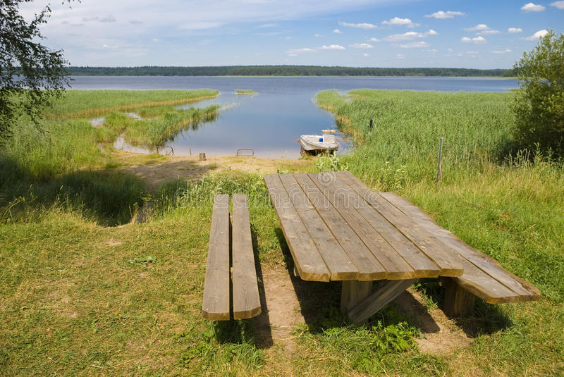 Wooden table with benches on the shore of lake royalty free stock images