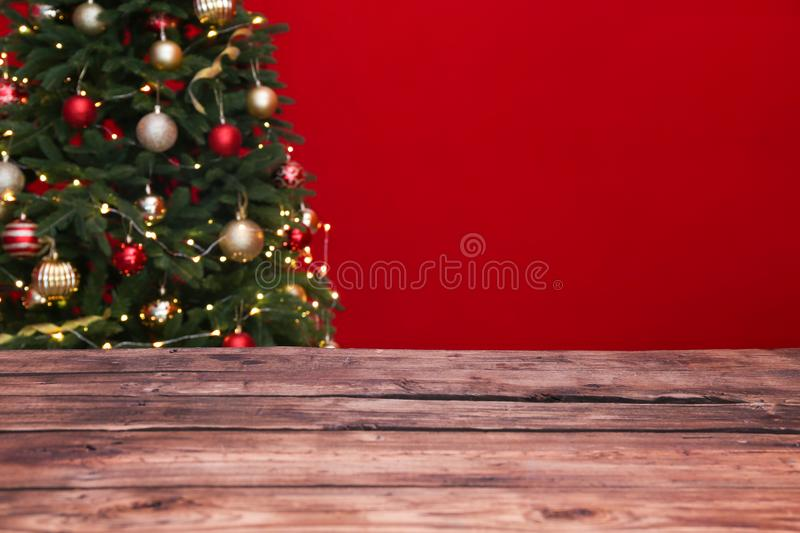 Wooden table and blurred Christmas tree with fairy lights royalty free stock image