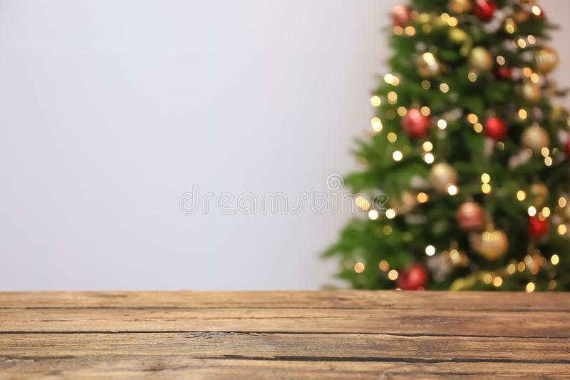 Wooden table and blurred Christmas tree royalty free stock photography