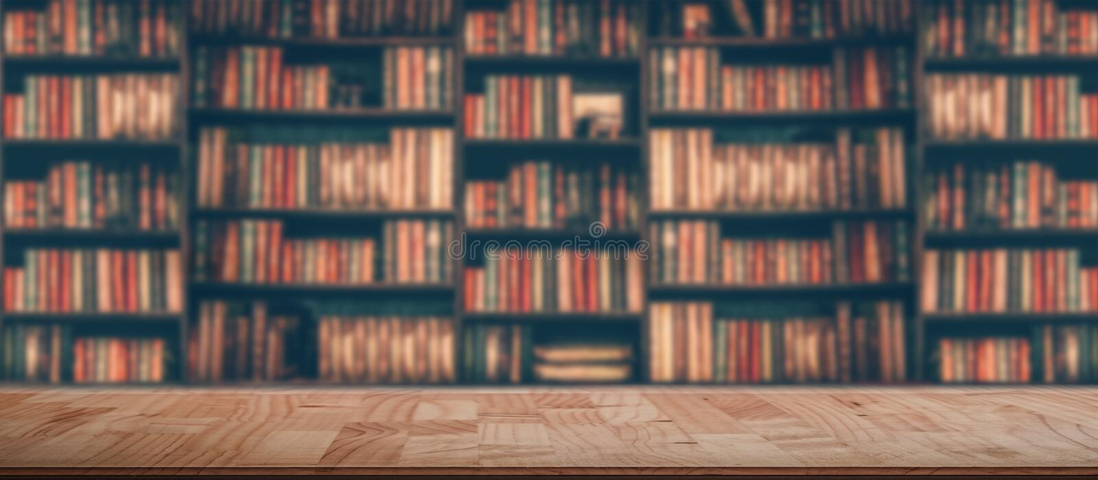 Wooden table in blurred Image Many old books on bookshelf in library royalty free stock photos