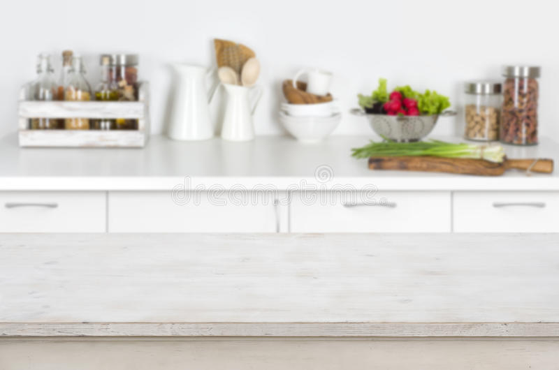 Wooden table on blurred kitchen interior background with fresh vegetables royalty free stock image