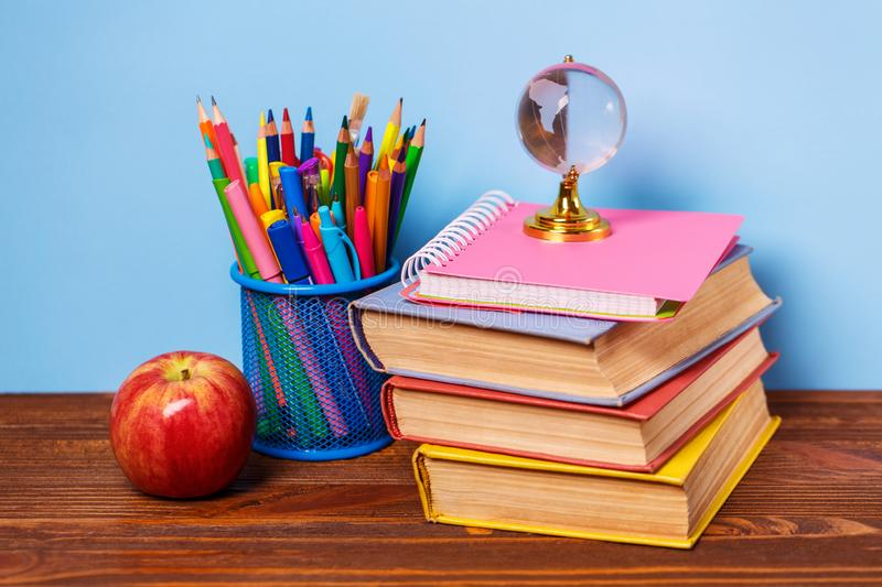 On a wooden table books, an apple and a globe stock image