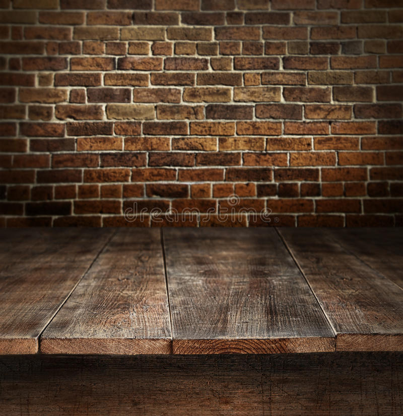 Wooden table with brick background stock photo