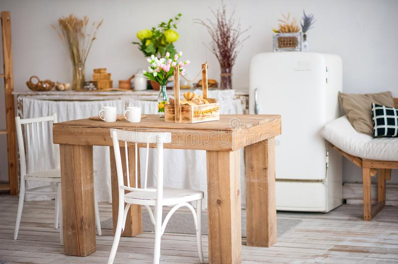 Wooden table in a bright rustic-style kitchen. Scandinavian style in the int. Erior of the kitchen stock image