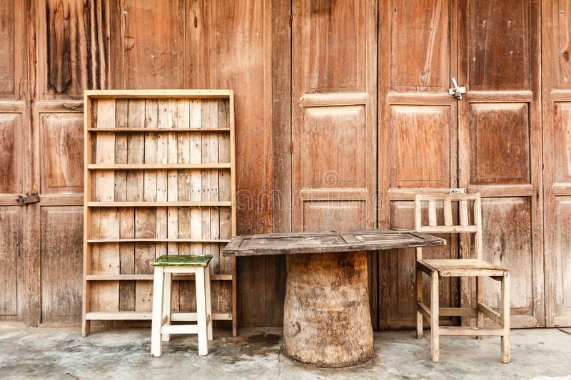 Wooden table,chairs,shelf in front of wooden house royalty free stock photography