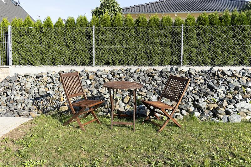 A wooden table with chairs stands outside on a green lawn. Home furniture for relaxing and eating outside. Mesh fence with stones. Fence from neighbors royalty free stock image