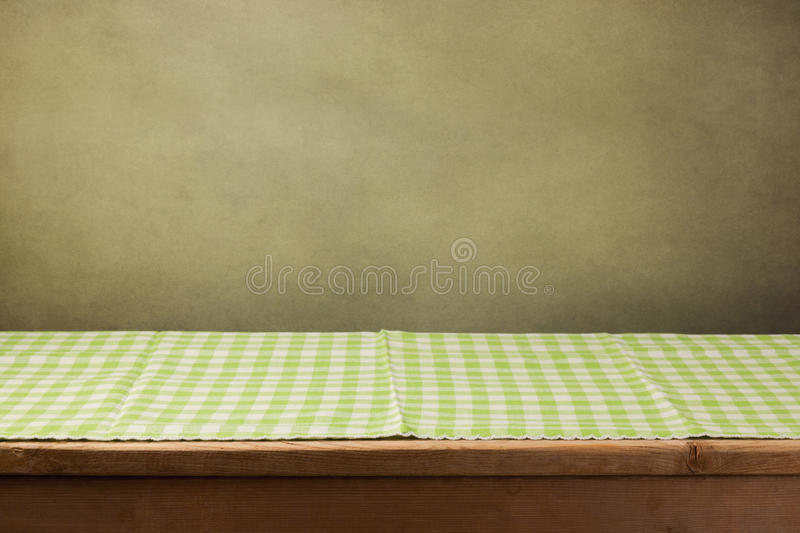 Wooden table with checked green tablecloth. Over retro background royalty free stock photo